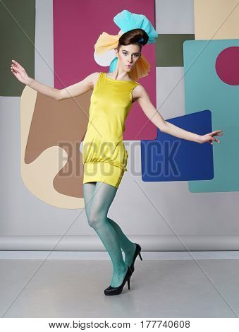 The eccentric girl is dancing on the background color. She is dressed in a short yellow dress, green pantyhose, high heels. View from the back. Back background: circles, chair for eggs.