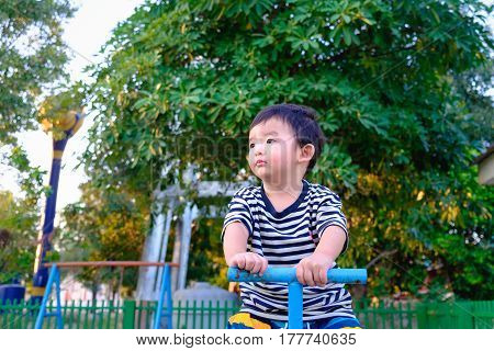 Sad Asian Kid Riding Seesaw Board At The Playground Under Sunlight,