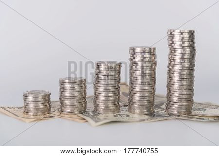 Increasing Columns Of Coins, Piles Of Coins Arranged As A Graph And Dollar Currency On White Backgro