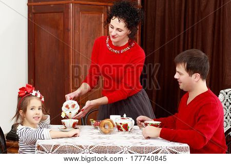 A family of three in the interior of the fifties of the last century, drinking tea for lace tablecloth vintage oak table.