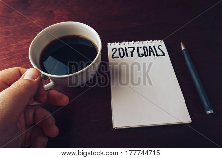 2017 goals list with notebook, man's hand with cup of coffee on wooden table. motivation and strategy concept. Top view.