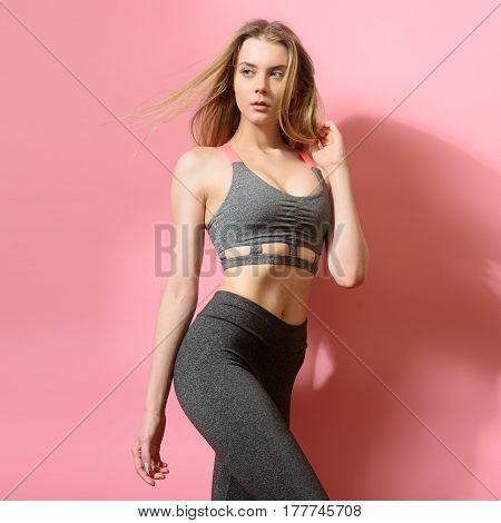 Beautiful fitness model girl posing wearing sport clothes. Girl in the sport concept.