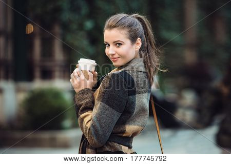 Beautiful businesswoman holding coffee cup and walking on city street to the work at spring time. Lifestyle shoot of cute adult woman.