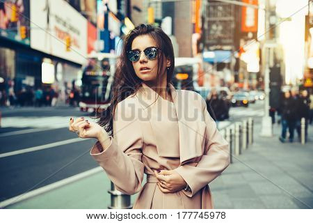 Fashionable girl walking on New York City street in Midtown wearing sunglasses and ping jacket.