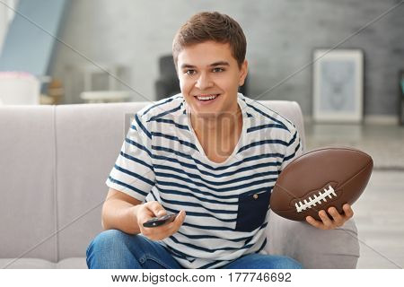 Teenager watching rugby at home