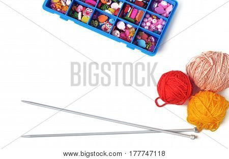 Spokes for knitting a box with accessories and scissors on a white background.Top view. Horizontal format. Indoors. Color. Photo.