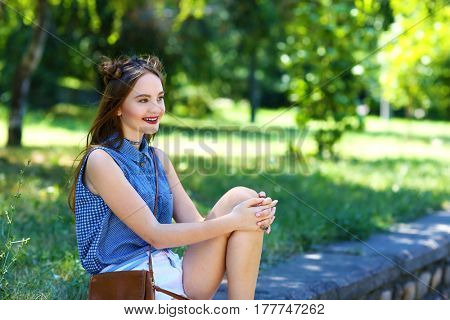 Beautiful teenage girl sitting on parapet