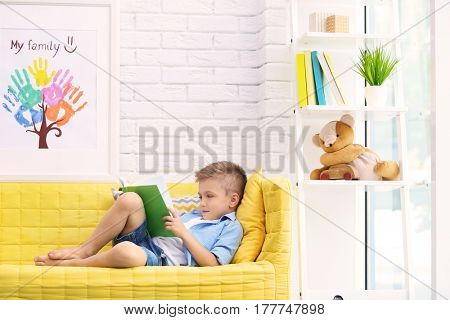 Cute boy reading book on sofa in living room