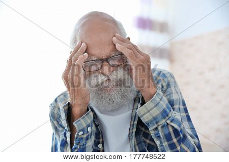 Senior man with headache, closeup