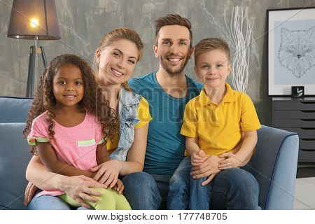 Happy interracial family sitting on sofa