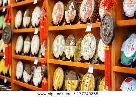 Disks Of Yunnan Puer On Wooden Shelves At Tea Shop, Lijiang