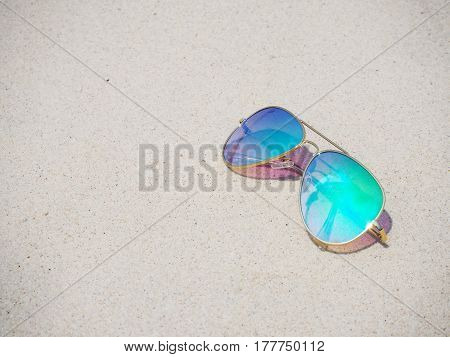 Fashionable mirror glasses on sand beach background