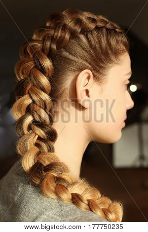 Young woman with beautiful hairstyle on blurred background