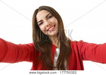 Beautiful young woman taking selfie on white background