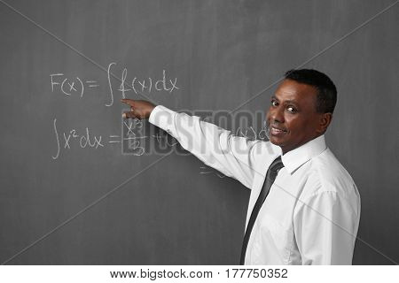 Confident Indian teacher explaining math formulas written on blackboard