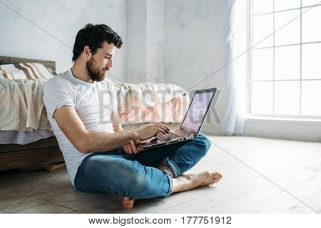 Young man sitting down on the floor near the bed with folded legs. Handsome cute guy is searching some information on laptop. Place for your logo or advert