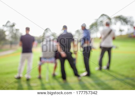 Blurred photo of unidentified people are looking the match in golf tournament.