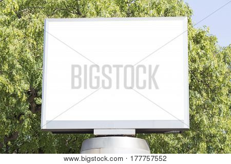 Blank billboard over a green trees background