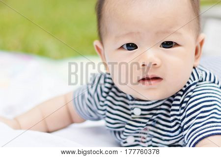 Asian Baby Lie Prone On Ground At Park
