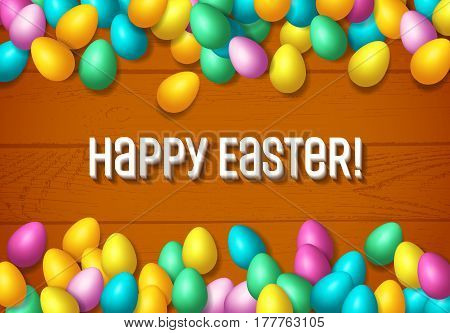 Easter frame with shiny colorful eggs spread over wooden background
