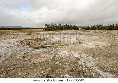 Blue sky with clouds over Opal Pool in the Midway Geyser Basin with the Firehole River in the background on the right