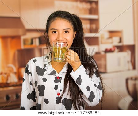 Young brunette woman posing in pyjamas and facing camera while drinking morning tea happily.