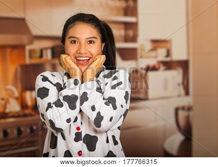 Young brunette woman posing in pyjamas and facing camera while touching face using hands, looking tired smiling.