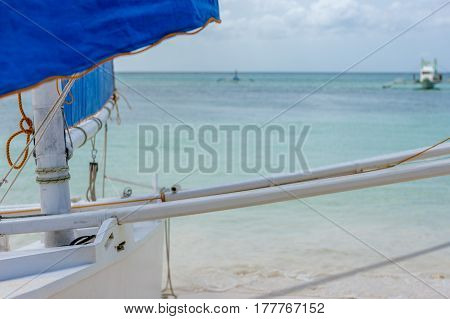 Foreground focus of a Philippines Filipino sail boat on the beach looking out to a calm clear sea with pump boats in the back ground.