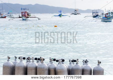A collection of scuba divers air taks on a tropical white sand beach with depth of field back ground of calm sea and pump boats.