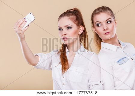 Fun bonding selfie concept. Sisters or best friends two student blonde girls taking self photo with smart phone camera having fun