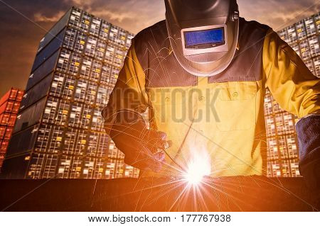 Industrial welding worker with safety equipments and protective mask welding steel structure with cargo container stack in background for transportation importexport and logistic industrial concept