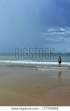 A young woman standing ankle deep in a tropical sea looking out at traditional filipino pump boats and the passing storm clouds.