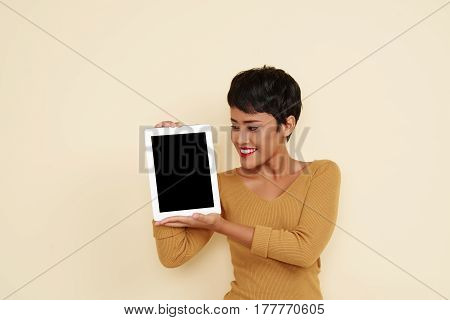 Smiling Filipino woman showing digital tablet with empty screen