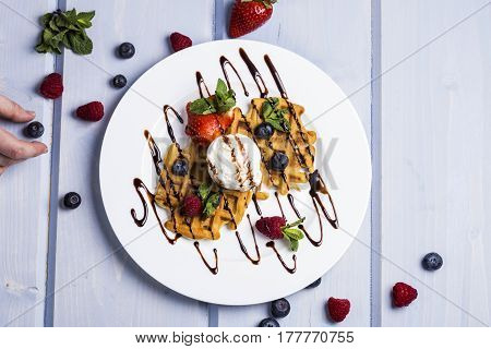 Plate of belgian waffles with ice cream chocolate sauce and fresh berries