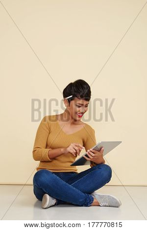 Pretty young woman with pencil behind her ear working on tablet computer