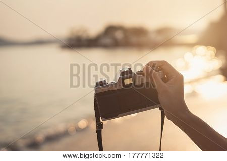 Hand holding camera to take photo of the beautiful sunset on the beach Travel concept