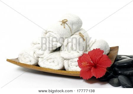 Towels stacked in wood bowl with flower, stone