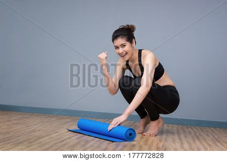 Young Asian Woman With Happy Smile Preparing Yoga Mat At Yoga Healthy Sport Gym. Yoga And Meditation