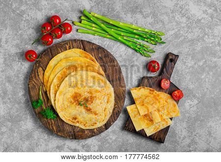 Stack of not sweet frying flour Flatbread Paratha roti tortillas. Ingredients for Flatbread Paratha roti cherry tomatoes asparagus parsley wooden board served on light gray background. Top view.