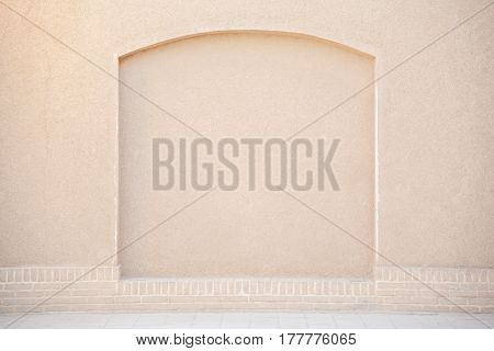 old grunge beige stucco wall with decorated arch shape use for background or backdrop in architecture or building concepts