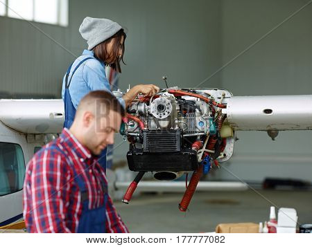 Female engineer with wrench repairing motor of jet