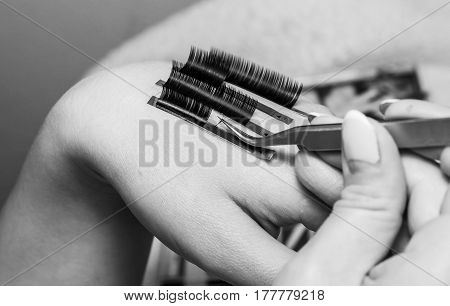 artificial eyelash extensions the master's hand eyelash extension procedure in a beauty salon the beauty industry is gushing into the hands of the masters