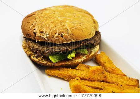 A gluten free organic hamburger with polenta and sweet potato fries