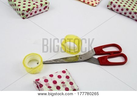 A scene of gift wrapping with gifts cellophane tape and scissors