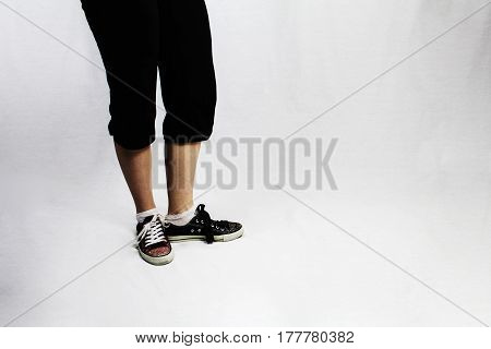 A female wearing the same style converse type trainers in different colours