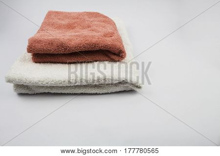 Two different coloured towels neatly folded studio isolated