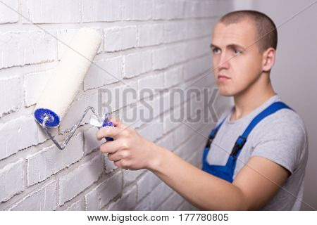 Young Handsome Man Painter In Workwear Painting Brick Wall With Paint Roller