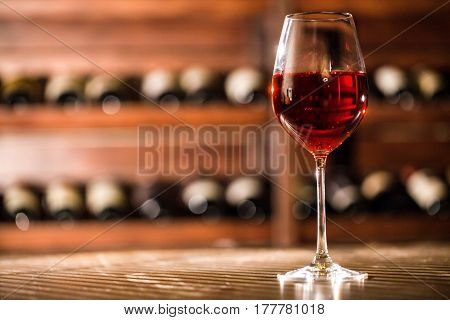 Wine glass with red wine in it placed on the table on the wine shelves background.