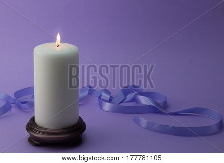 White lit candle with lilac ribbon and background