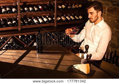 Handsome man looking at glass of wine and smiling. Man sitting by the table in a wine vault